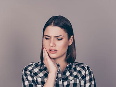 woman holding side of her face in pain